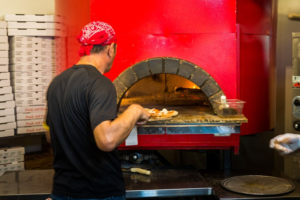 chef placing a pizza in a brick oven