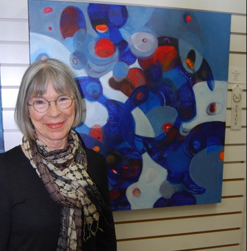 A Woman Standing Next To Some Hanging Art Work