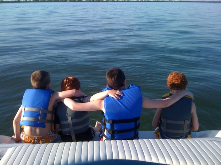 Four children sitting on the back of a boat