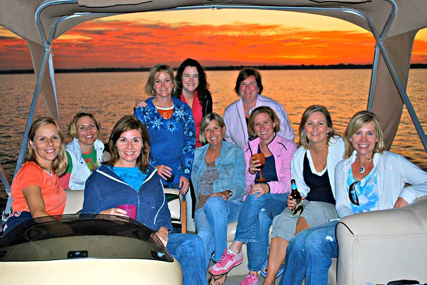 A group of women on a boat at sunset