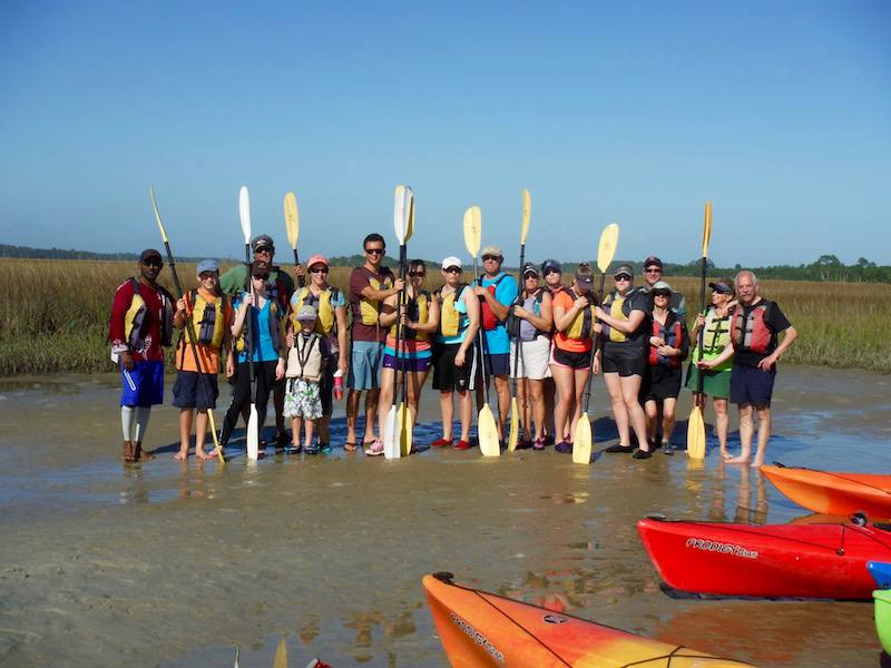a group of people holding kayak paddles