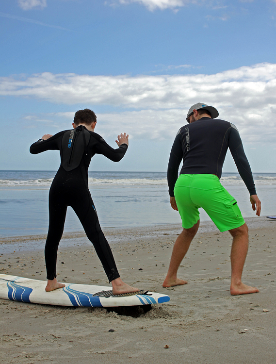 a kid learning how to surf with an instructor