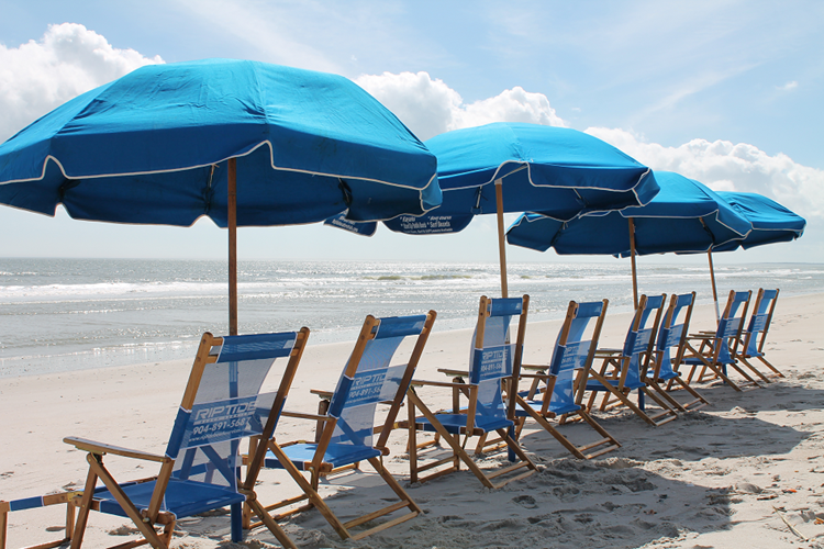 a row of deck chairs on a beach