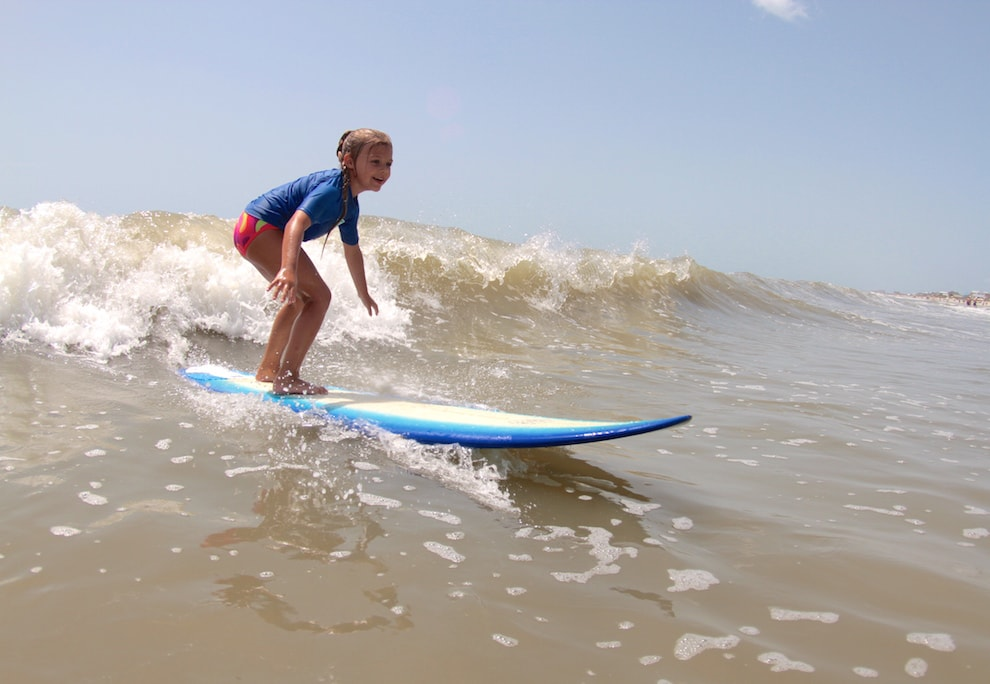 a young girl surfing a wave at surf school