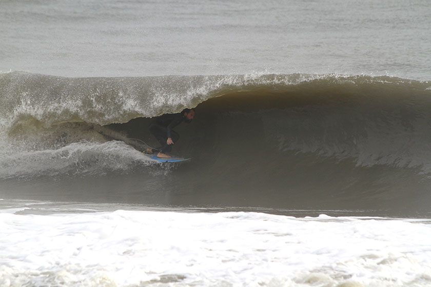 a surf instructor riding a tube wave