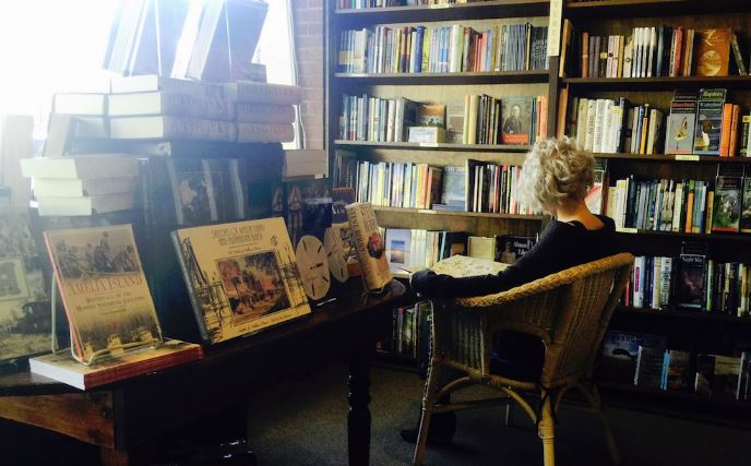 a person sitting in a chair in the book shop reading a book