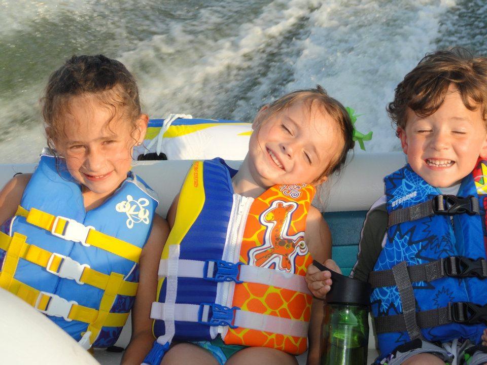 Three children on a boat relaxing
