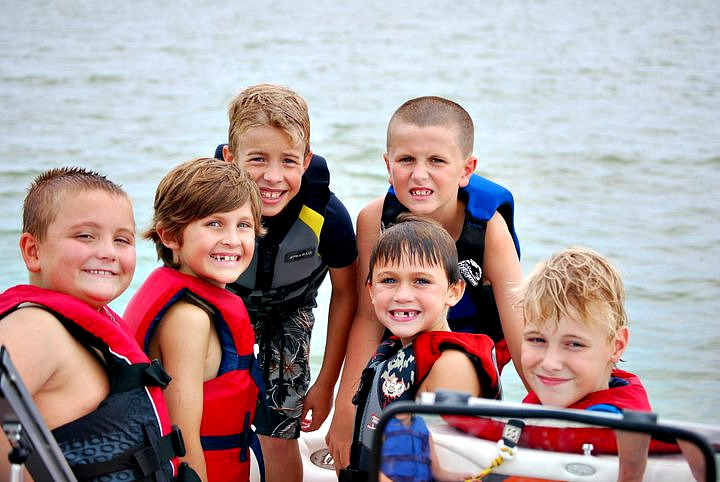 A group of children on a boat wearing life jackets