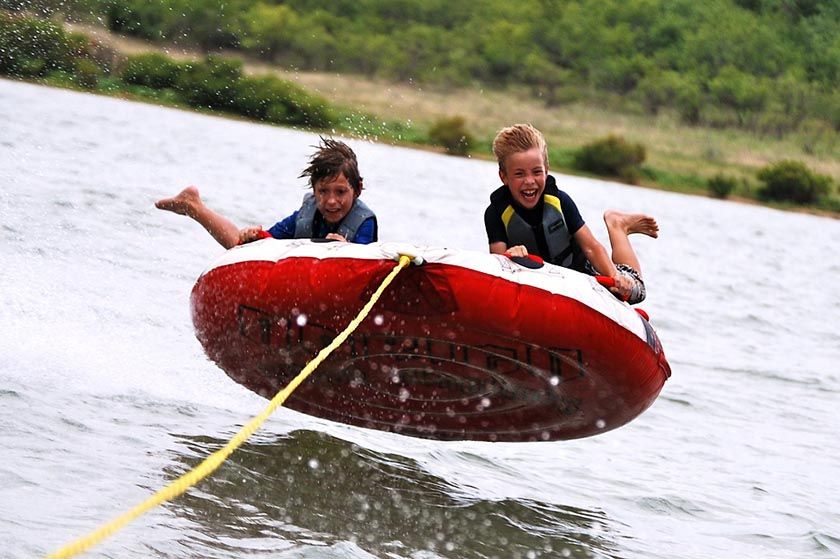 Two boys on a tube being pulled by a boat