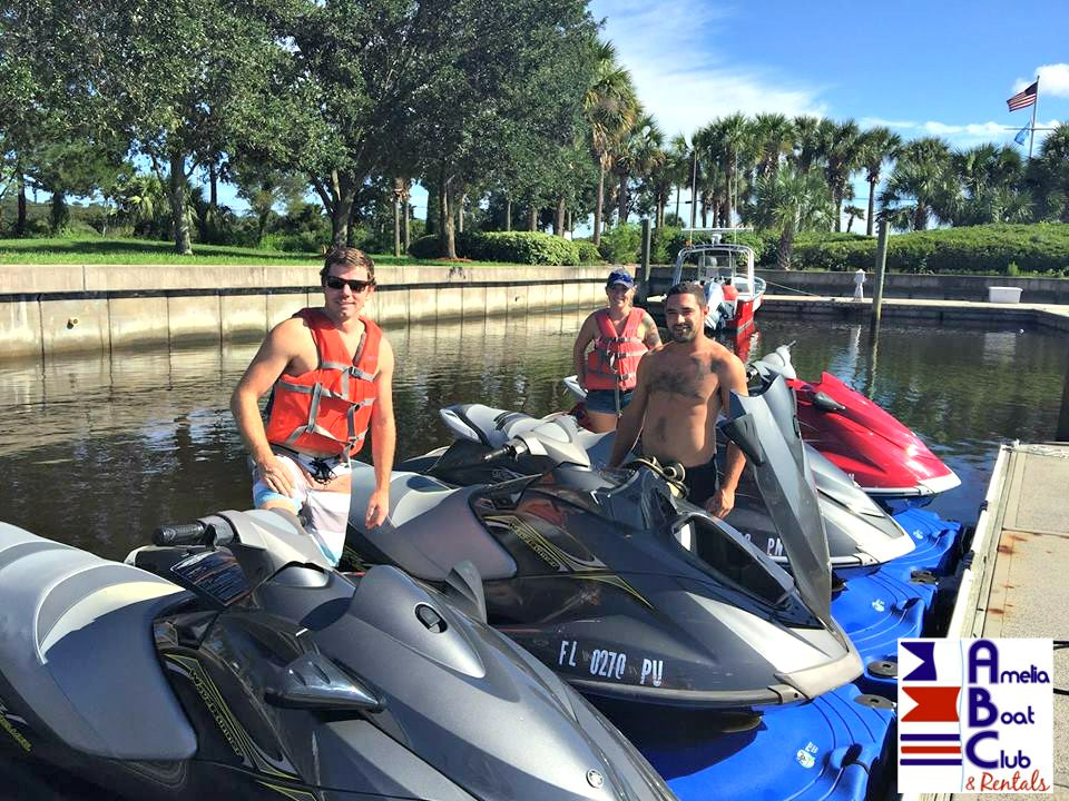 three people getting ready to go jet skiing