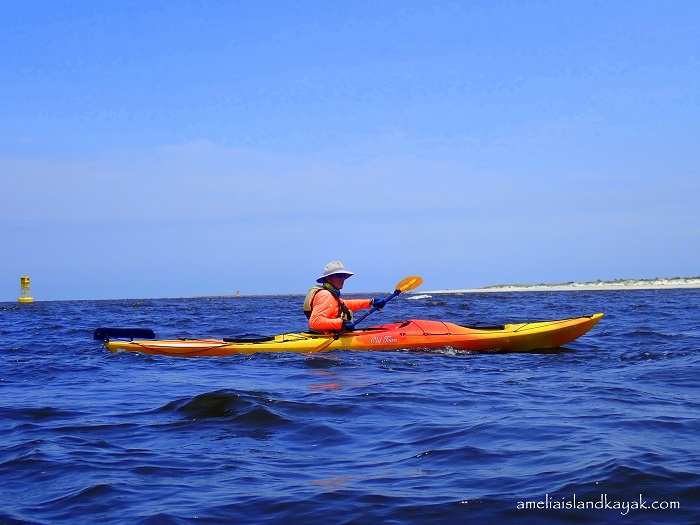 a man kayaking on the ocean